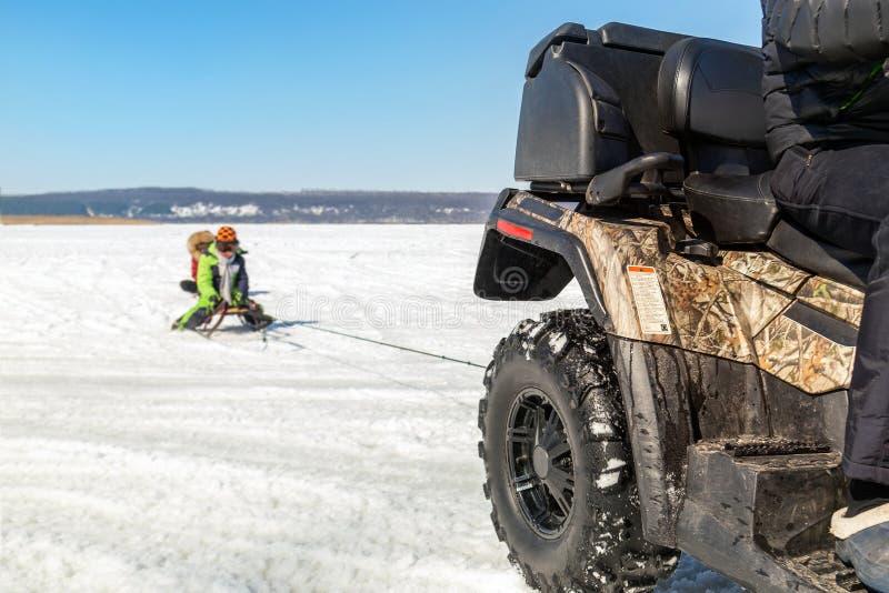 Hombre en los trineos que montan del quadbike de ATV con los niños a remolque en superficie congelada del lago en el invierno Dep fotografía de archivo