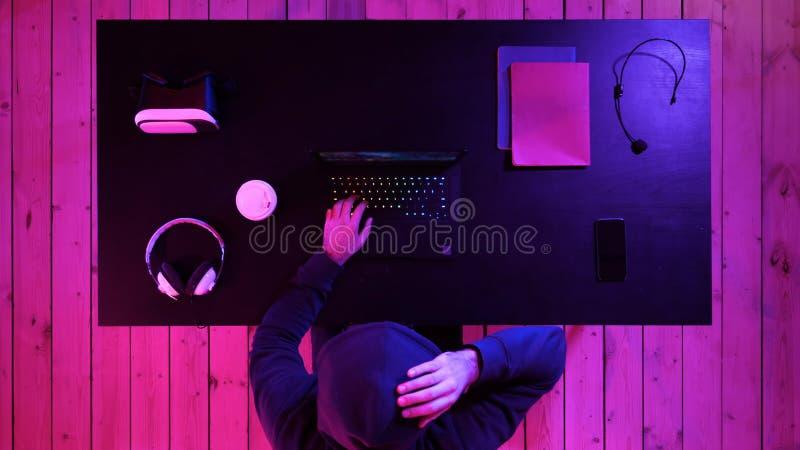 Hombre en los vidrios que juegan a un juego en el ordenador portátil fotografía de archivo