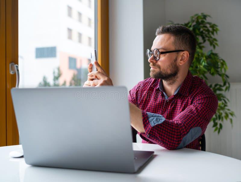 Hombre en los vidrios que sientan en casa la oficina y que trabajan en un ordenador portátil y que usan smartphone imagen de archivo libre de regalías