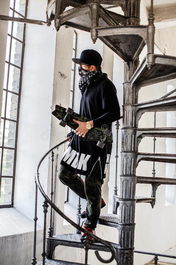 Hombre en máscara del gángster con el monopatín imagenes de archivo