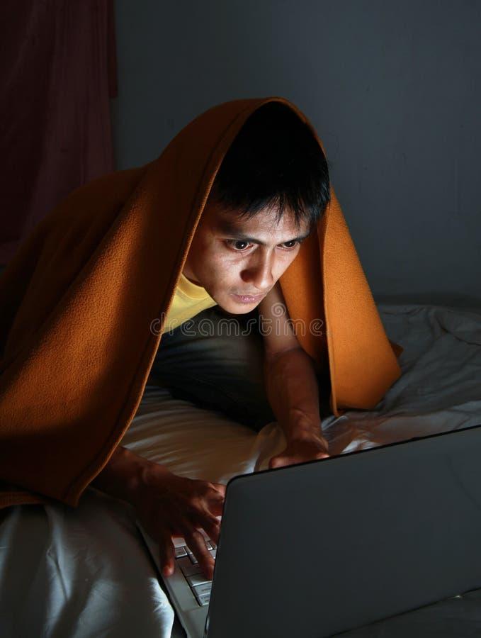 Hombre en manta usando la computadora portátil imagen de archivo libre de regalías