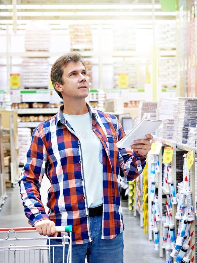 Hombre en materiales de construcción de tienda foto de archivo