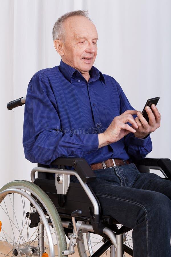 Hombre en mensaje de texto de la silla de ruedas que enarena imagenes de archivo