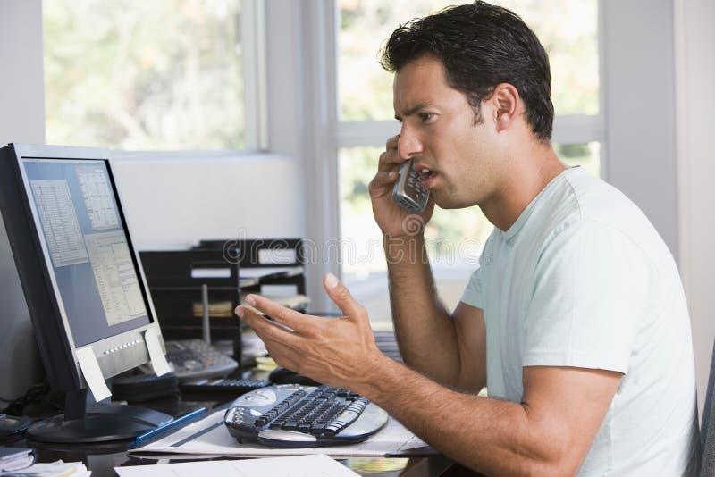 Hombre en Ministerio del Interior en el teléfono usando el ordenador foto de archivo