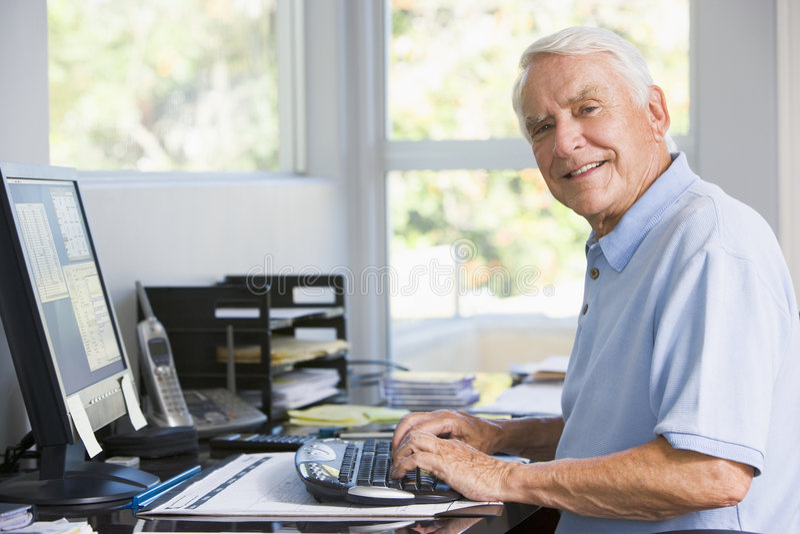Hombre en Ministerio del Interior usando la sonrisa del ordenador foto de archivo