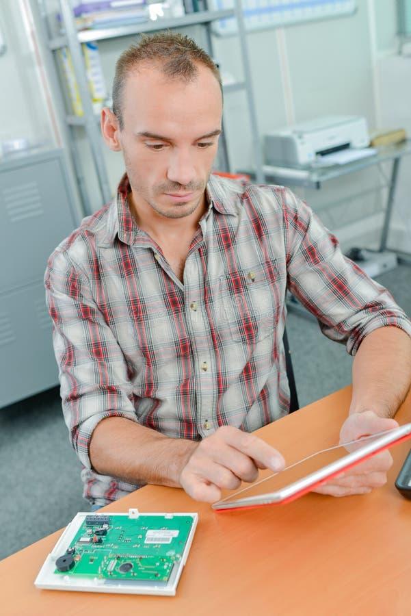 Hombre en oficina en la tableta imagen de archivo