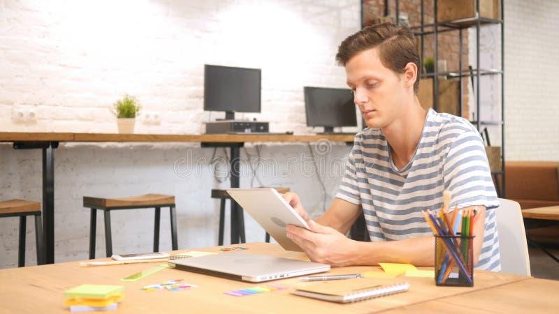 Hombre en oficina usando la tableta de Digitaces, diseñador creativo, agencia fotografía de archivo libre de regalías