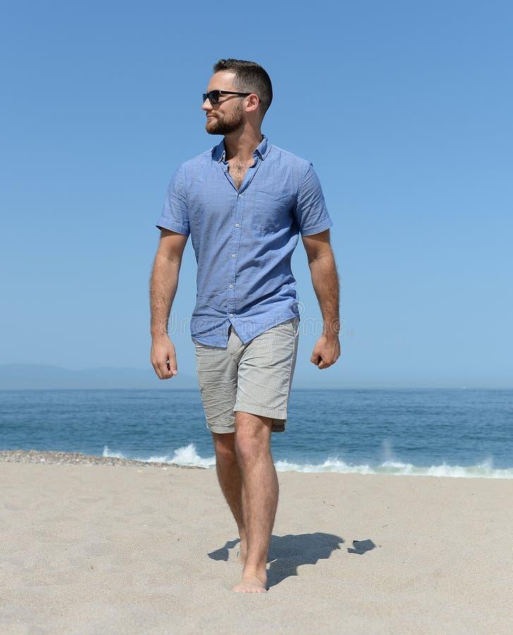Hombre en pantalones cortos que camina en la playa foto de archivo libre de regalías