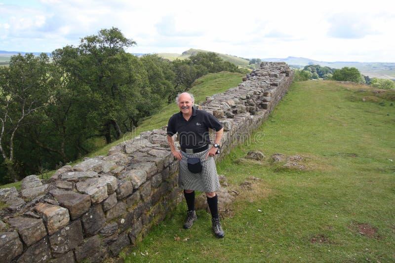 Hombre en pared de piedra que hace una pausa de la falda escocesa foto de archivo