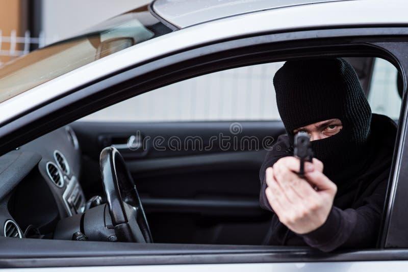 Hombre en pasamontañas negro con la arma de mano que conduce un coche fotografía de archivo
