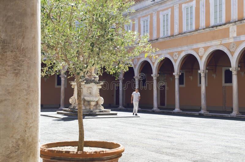 Hombre en patio viejo con cámaras acorazadas y una estatua, en Pisa, Italia imagenes de archivo