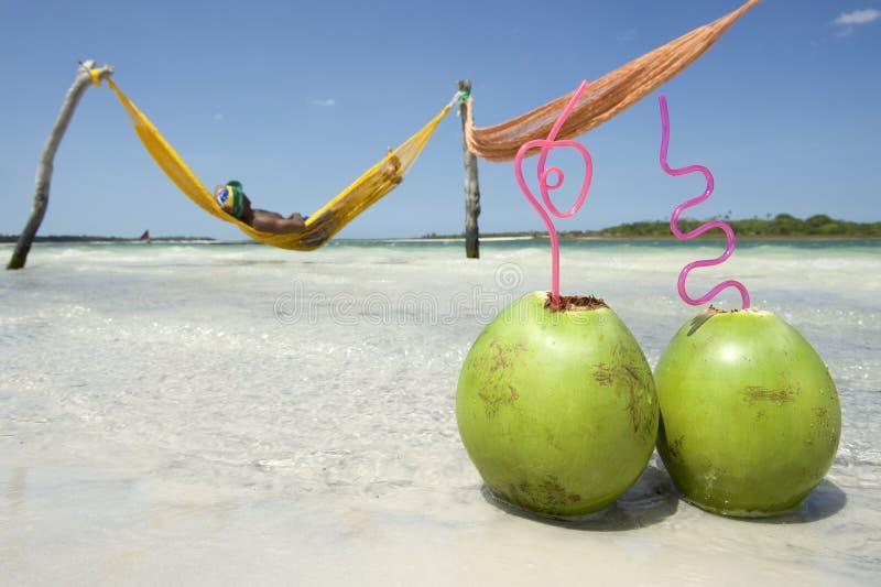 Hombre en playa brasileña de la hamaca con los cocos imagenes de archivo