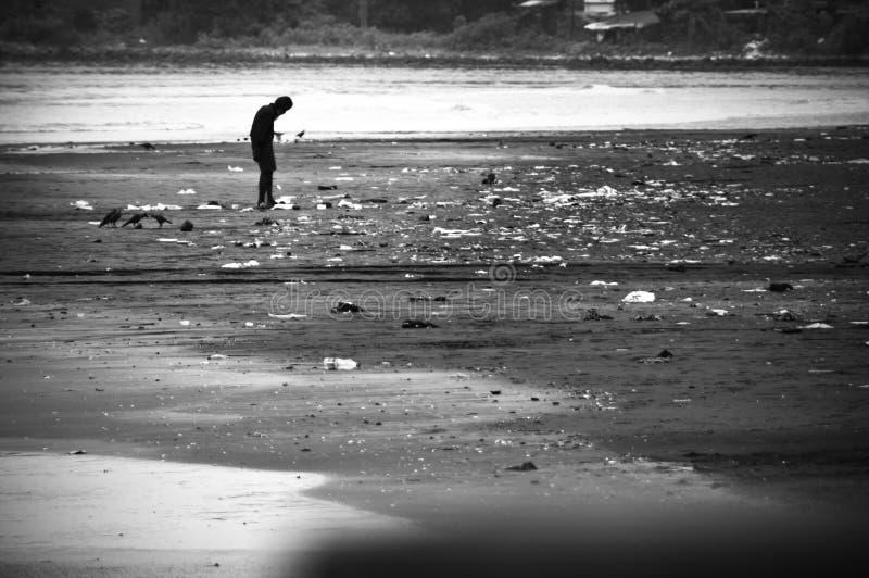 Hombre en pobreza que camina en la playa contaminada imagen de archivo