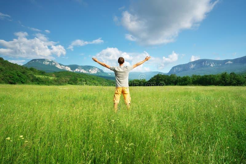 Hombre en prado verde imagen de archivo