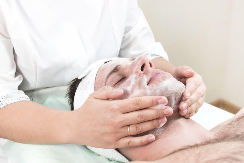 Hombre en procedimiento cosmético de la máscara en salón del balneario imagen de archivo