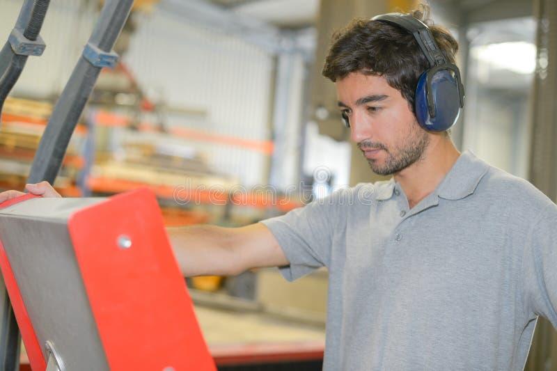 Hombre en protectores contra el ruido de la fábrica que llevan imagen de archivo