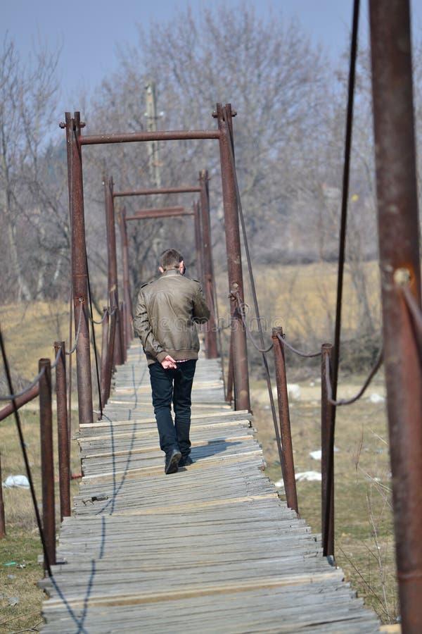 Hombre en puente colgante foto de archivo libre de regalías