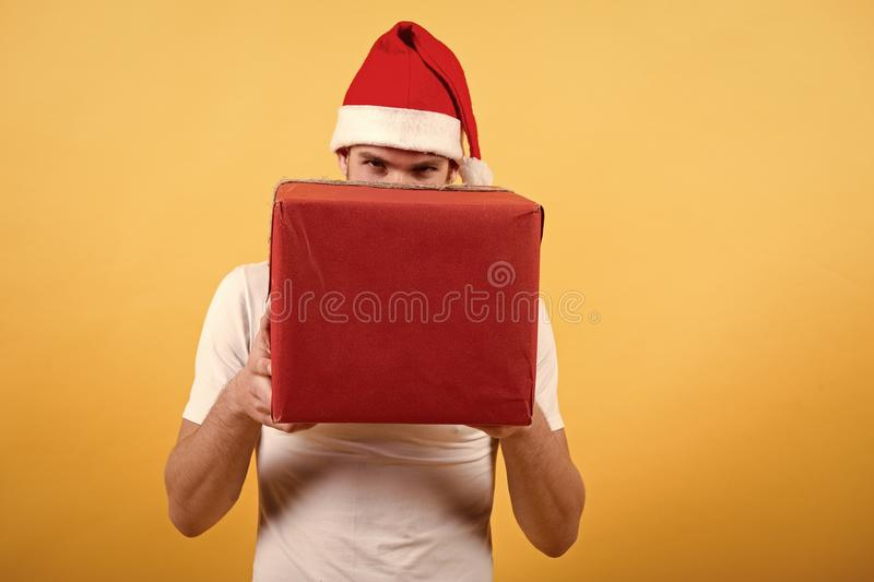 Hombre en regalo de Navidad del control del sombrero de santa La ma?ana antes de Navidad hombre feliz de santa en la pared amaril fotos de archivo