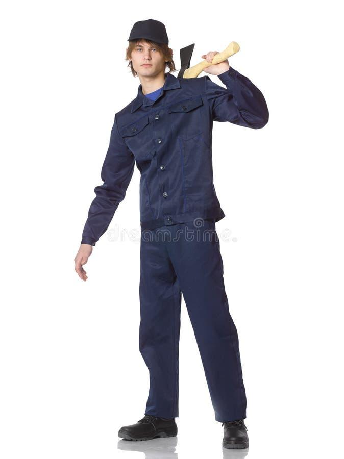 Hombre en reparador azul del traje en un campo con un hacha en su hombro imagen de archivo