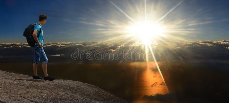 Hombre en roca sunshining sobre las nubes tempestuosas imagen de archivo libre de regalías