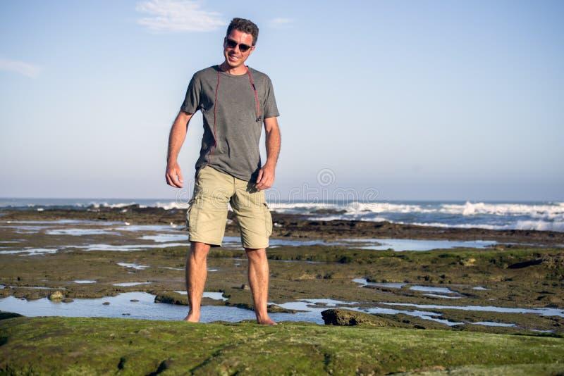 Hombre en rocas por el océano fotografía de archivo libre de regalías