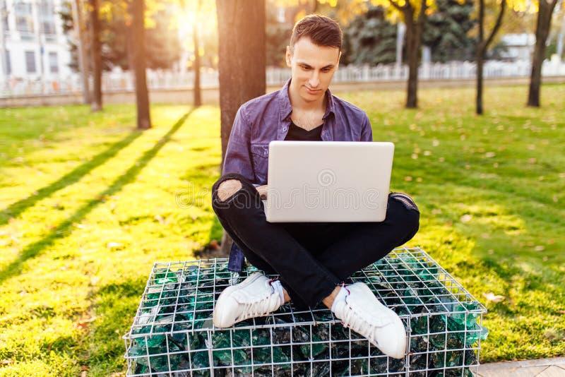 Hombre, en ropa casual, sentándose en un banco, trabajando con un lapto fotografía de archivo