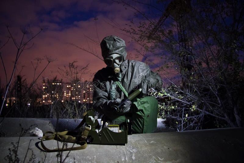Hombre en ropa química protectora y careta antigás aislada con el dispositivo de detección químico en zona de la contaminación qu imágenes de archivo libres de regalías