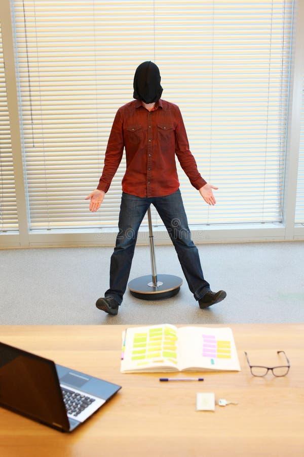Hombre en saco negro en la cabeza que reflexiona sobre la silla neumática imagen de archivo