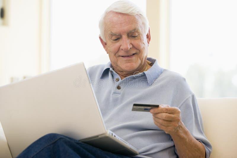 Hombre en sala de estar con la computadora portátil y de la tarjeta de crédito imagen de archivo