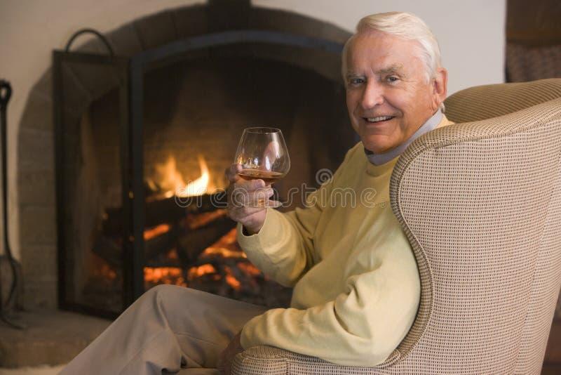 Hombre en sala de estar con la sonrisa de la bebida imágenes de archivo libres de regalías
