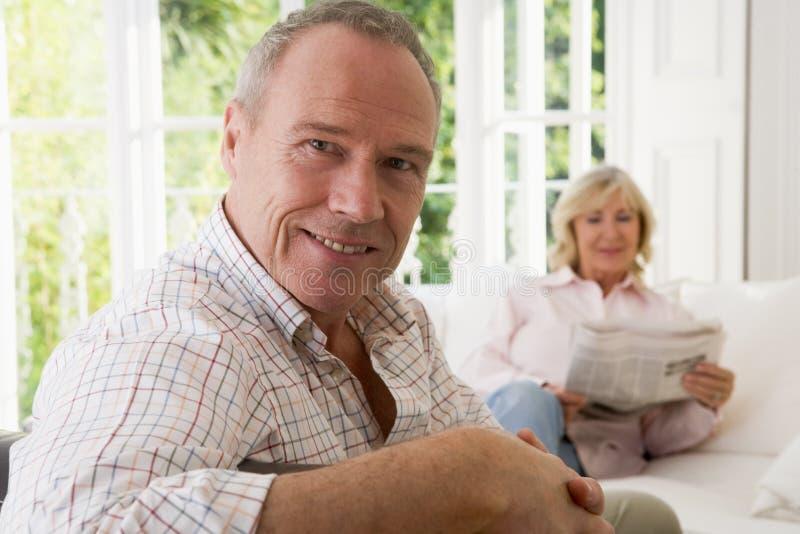 Hombre en sala de estar que sonríe con la mujer fotos de archivo libres de regalías