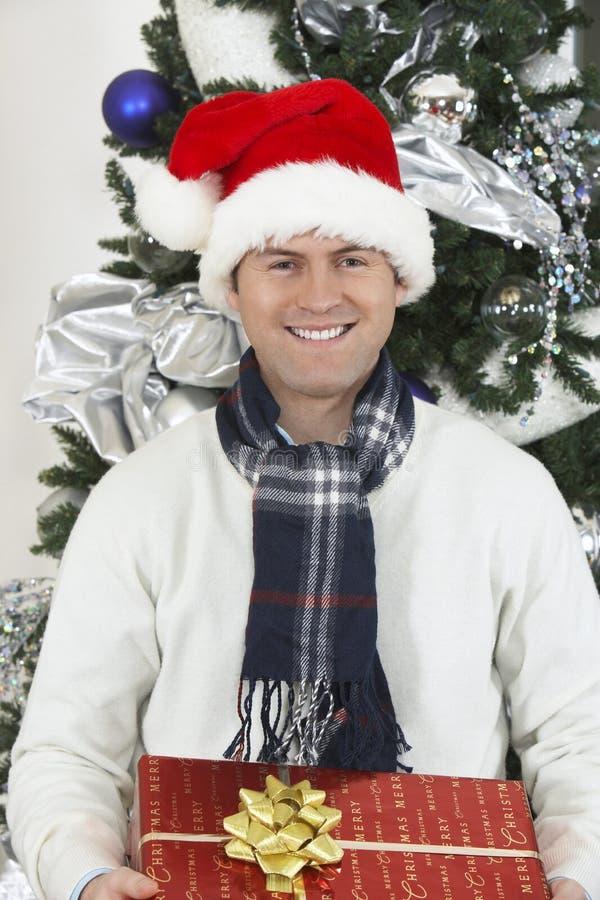 Hombre en Santa Cap Holding Gift Box por el árbol de navidad fotografía de archivo libre de regalías