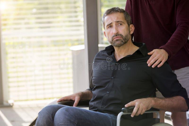 Hombre en silla de ruedas con un ayudante que parece triste fotos de archivo libres de regalías