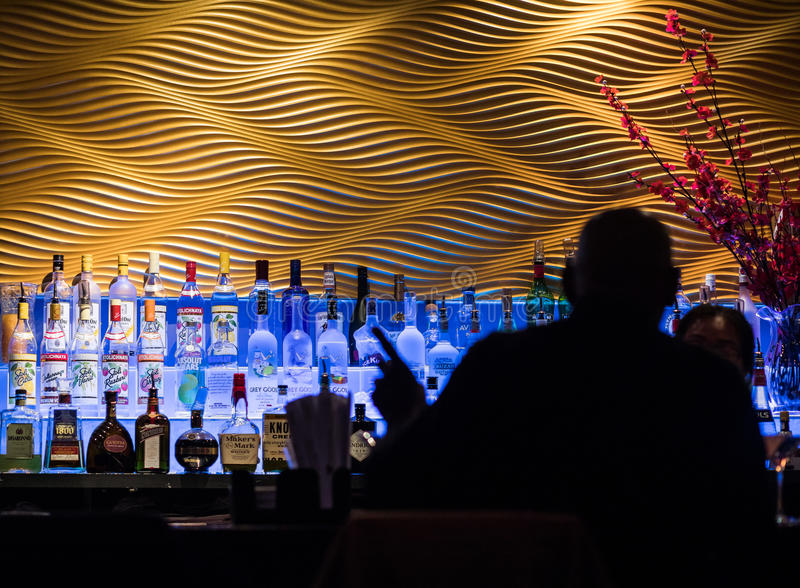 Hombre en silueta en la barra que pide una bebida en un sushi Restaur foto de archivo libre de regalías