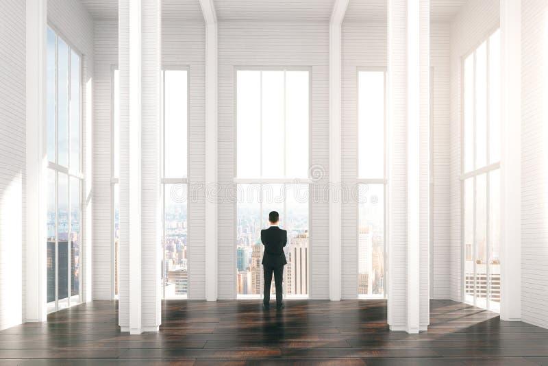 Hombre en sitio soleado moderno del diseño del desván con la opinión de la ciudad foto de archivo libre de regalías