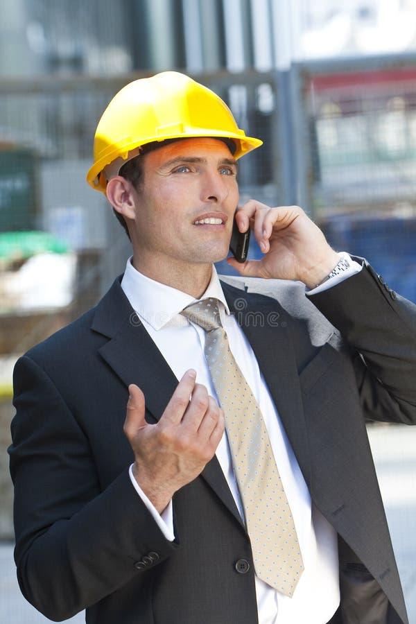 Hombre en sombrero duro industrial que habla en el teléfono celular fotos de archivo