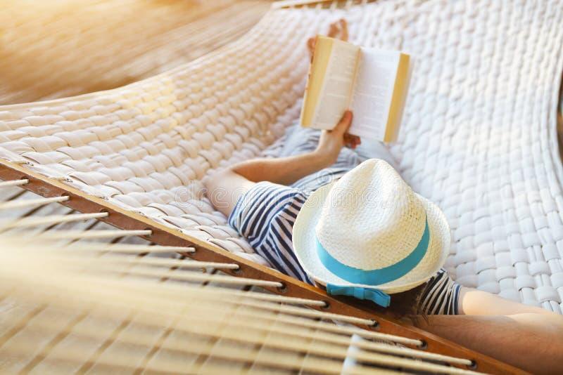 Hombre en sombrero en una hamaca con el libro en un día de verano imágenes de archivo libres de regalías