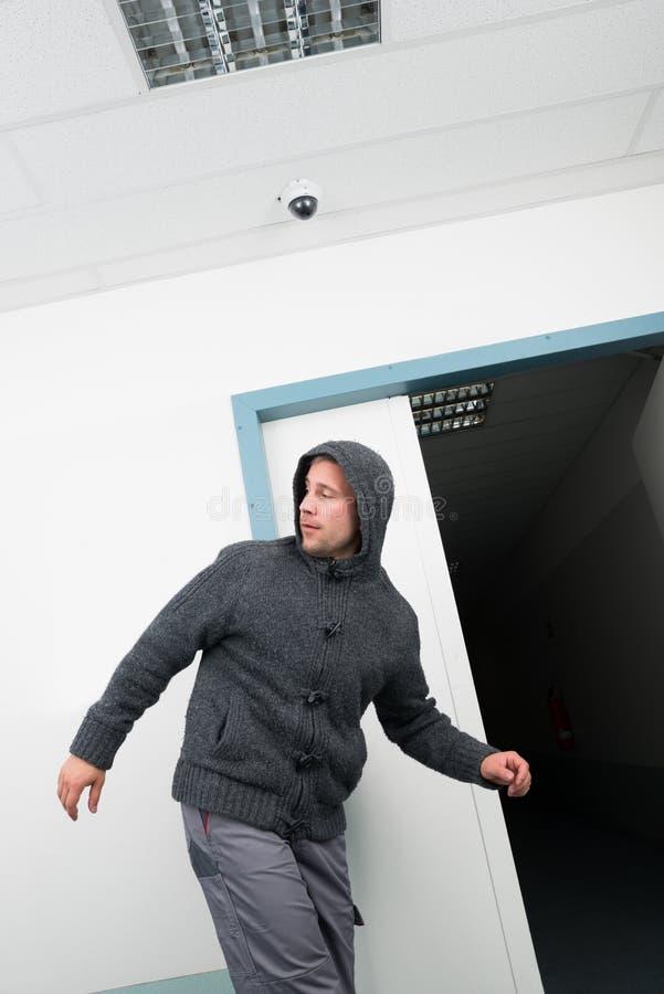 Hombre en sudadera con capucha que camina bajo área de vigilancia del cctv foto de archivo