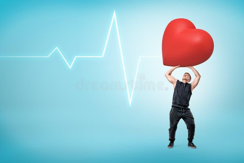 Hombre en sudadera con capucha sin mangas que soporta el corazón rojo pesado grande en fondo azul claro con el espacio de la líne imágenes de archivo libres de regalías