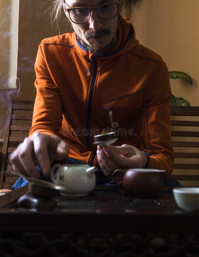 Hombre en té exquisito del brebaje en tetera en la ceremonia de té del chino tradicional Sistema de equipo fotos de archivo libres de regalías