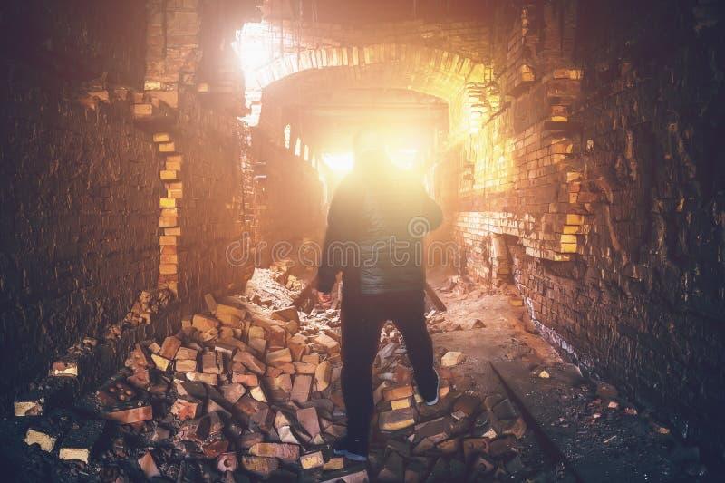 Hombre en túnel subterráneo arruinado abandonado, luz del extremo o salida del pasillo espeluznante del ladrillo, mina rota indus fotos de archivo libres de regalías