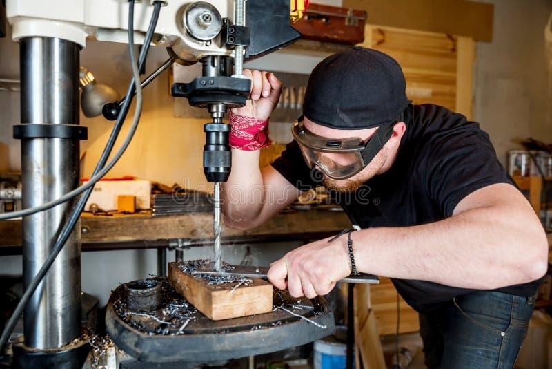 Hombre en trabajo sobre la prensa de taladro eléctrico foto de archivo