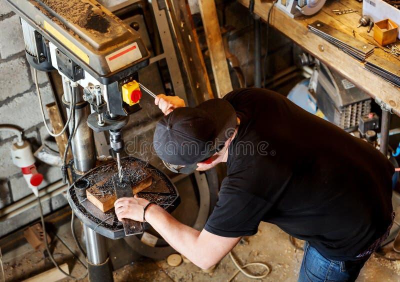 Hombre en trabajo sobre la prensa de taladro eléctrico fotos de archivo libres de regalías