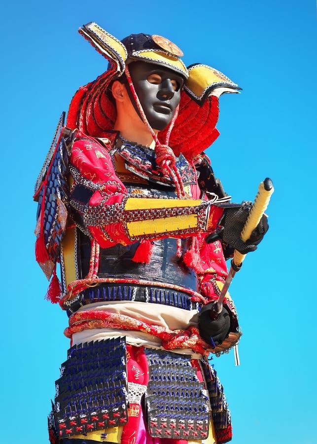 Hombre en traje del samurai con la espada en fondo del cielo azul imágenes de archivo libres de regalías