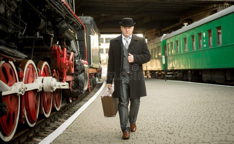 Hombre en traje retro con la maleta que camina en la plataforma del tren imágenes de archivo libres de regalías