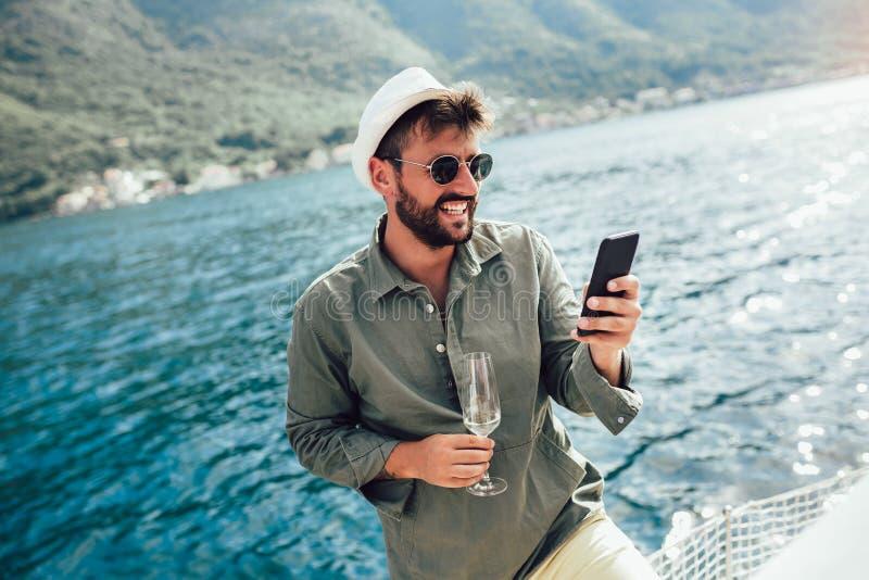 Hombre en un barco de navegación usando el teléfono fotografía de archivo