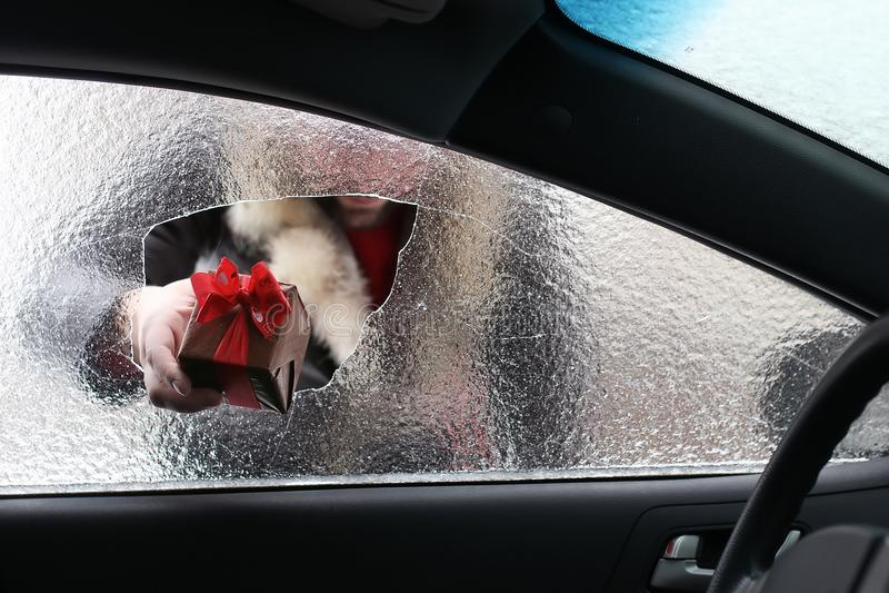 Hombre en un casquillo rojo de Santa Claus en un coche con el vidrio quebrado fotos de archivo