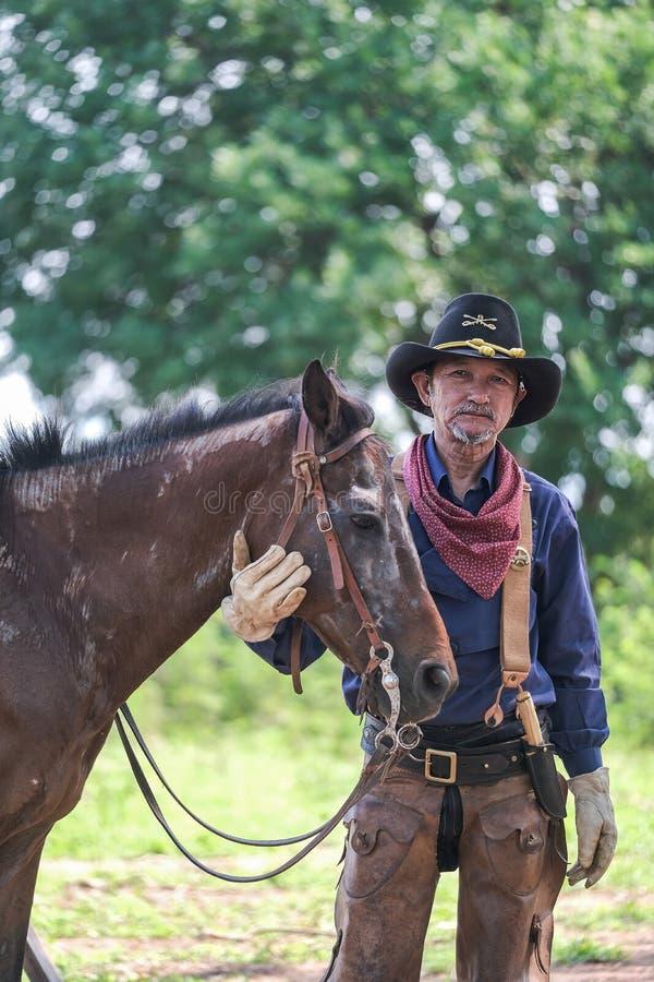 Hombre en un equipo del vaquero con su caballo fotografía de archivo libre de regalías