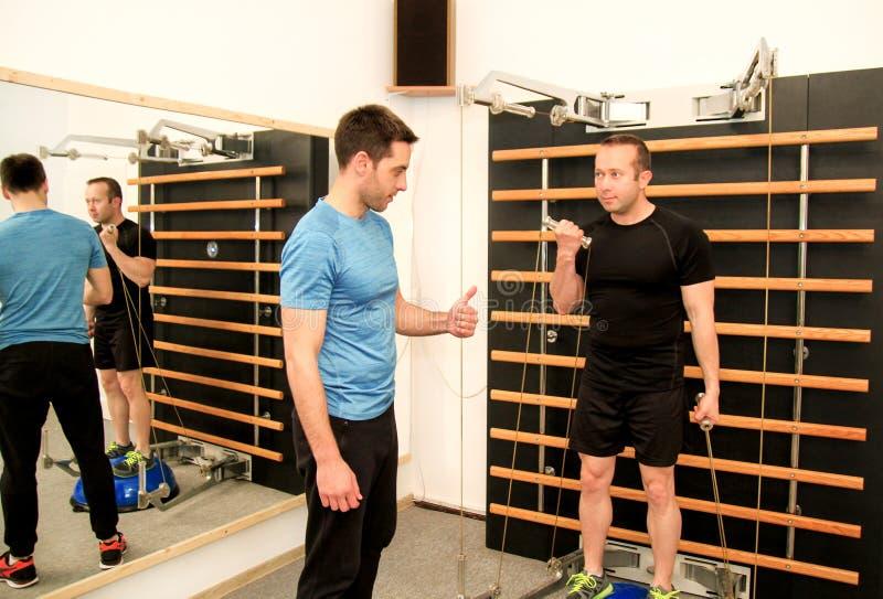 Hombre en un gimnasio con la ayuda de su instructor foto de archivo