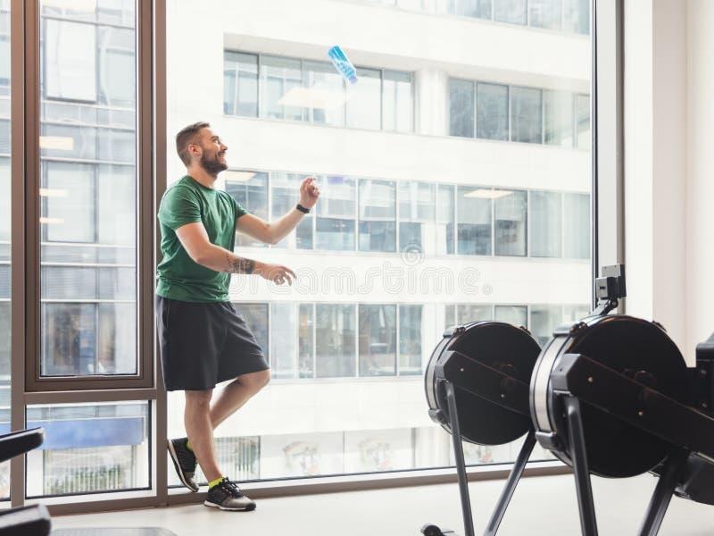 Hombre en un gimnasio que lanza una botella para arriba en el aire imagen de archivo libre de regalías